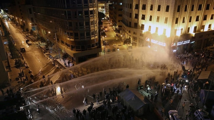 Lebanese activists shout anti-government slogans as they are sprayed by riot police using water cannons during a protest against the ongoing trash crisis, in downtown Beirut, Lebanon, Saturday, Aug. 22, 2015. Police have unleashed tear gas and water cannons on thousands of Lebanese demonstrating in downtown Beirut against government corruption and political dysfunction that has left garbage accumulating in the streets in suburbs of the capital for over a month. (AP Photo/Bilal Hussein)