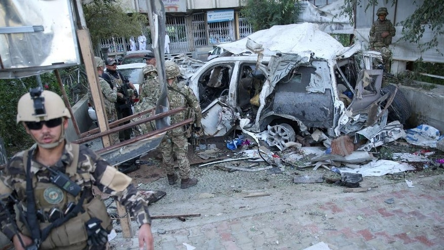 Aug. 22, 2015, photo shows Afghan security forces and British soldiers inspecting  site of a suicide attack in Kabul that killed 12 people, including 3 American contractors(AP Photo/Massoud Hossaini)
