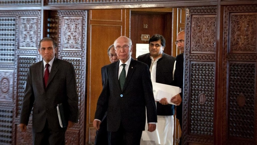 Pakistan's National Security Adviser Sartaj Aziz, center, arrives with top officials of Foreign Ministry for a press conference in Islamabad, Pakistan, Saturday, Aug. 22, 2015. Aziz says he is still ready to travel to New Delhi for Sunday's security talks with his counterpart despite fresh tensions between the longtime adversaries. (AP Photo/Anjum Naveed)