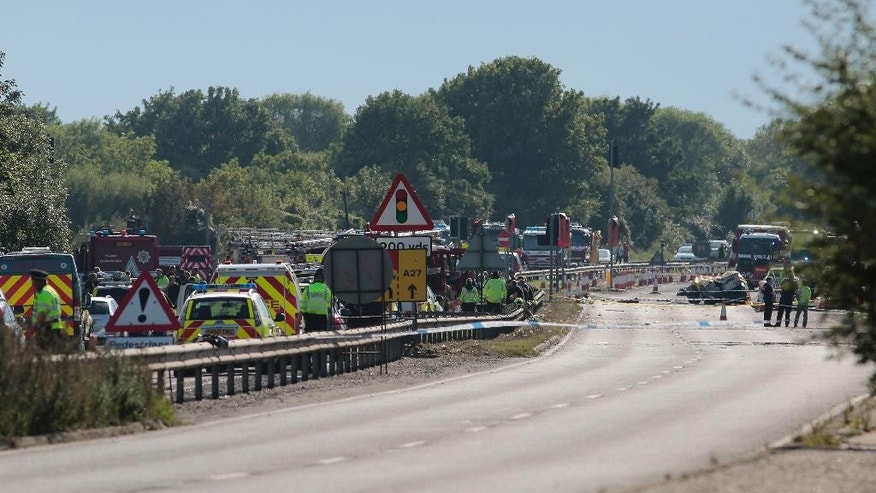 Emergency services attend the scene on the A27 road after a plane crashed into cars during an aerial display at the Shoreham Airshow in West Sussex, England, Saturday, Aug. 22, 2015. A military jet taking part in a British airshow crashed into a busy main road, killing and injuring several people, police said Saturday. Witnesses told local TV that the jet appeared to have plummeted when it failed to pull out of a loop maneuver. (Daniel Leal-Olivas/PA via AP) UNITED KINGDOM OUT, NO SALES, NO ARCHIVE