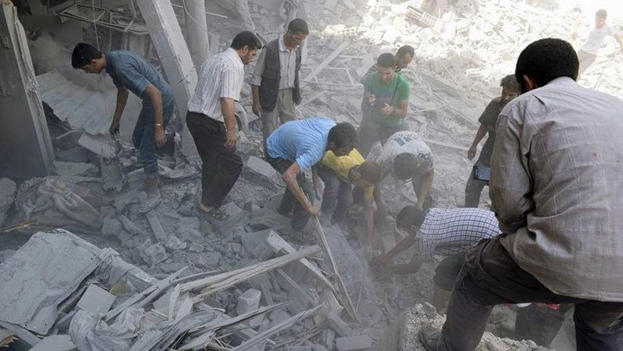This photo released by the Douma Revolution News Network on their Facebook page, shows Syrians looking for bodies under debris of destroyed buildings following a Syrian government airstrike on the Damascus suburb of Douma, Syria, Saturday, Aug. 22, 2015. Syrian activists said that at least 20 people have been killed and dozens wounded in government airstrikes on Douma. (Firas Abdullah/Douma Revolution News Network Facebook page via AP)