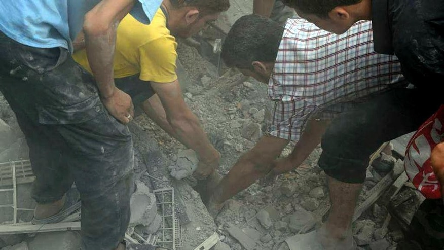 This photo released by the Douma Revolution News Network on their Facebook page, shows Syrians trying to remove a body trapped under debris of destroyed buildings following a Syrian government airstrike on the Damascus suburb of Douma, Syria, Saturday, Aug. 22, 2015. Syrian activists said that at least 20 people have been killed and dozens wounded in government airstrikes on Douma. (Firas Abdullah/Douma Revolution News Network Facebook page via AP)