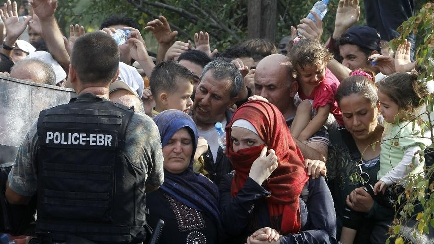 Migrants wait to enter Macedonia from Greece on the border line with Greece, near the southern Macedonia's town of Gevgelija, Friday, Aug. 21, 2015. About 39,000 people, mostly Syrian migrants, have been registered as passing through Macedonia in the past month, twice as many as the month before. (AP Photo/Boris Grdanoski)