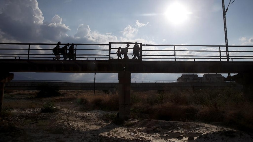 Silhouettes of migrants are seen walking along a railway bridge, after entering into Macedonia from Greece on their way towards EU, near the southern Macedonian town of Gevgelija, Friday, Aug. 21, 2015. About 39,000 people, mostly Syrian migrants, have been registered as passing through Macedonia in the past month, twice as many as the month before. They previously encountered little resistance at the border, but the recent influx has overwhelmed Macedonian authorities who this week declared a state of emergency and stopped many from crossing. (AP Photo/Boris Grdanoski)