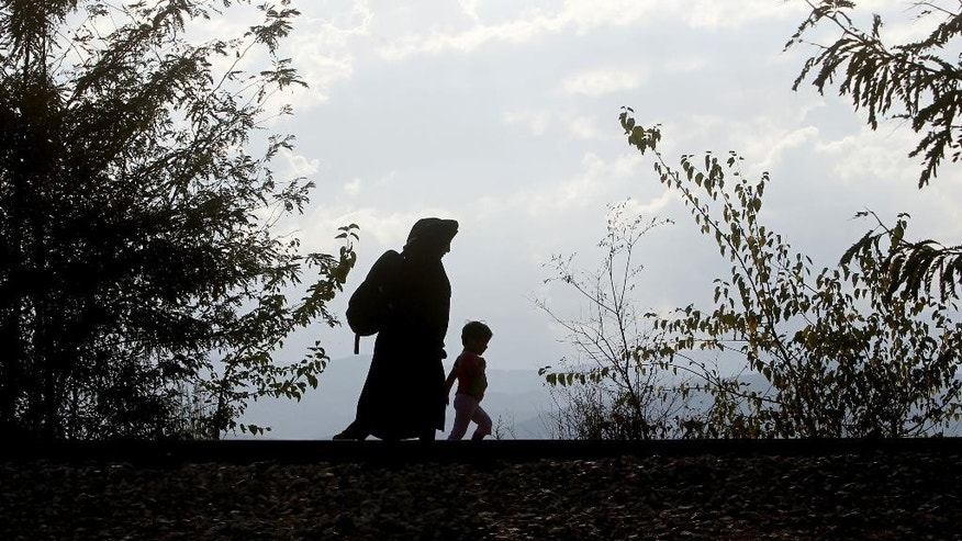 Silhouettes of a woman migrant with a child are seen walking along a railway tracks after entering into Macedonia from Greece on their way towards EU, near the southern Macedonian town of Gevgelija, Friday, Aug. 21, 2015. About 39,000 people, mostly Syrian migrants, have been registered as passing through Macedonia in the past month, twice as many as the month before. (AP Photo/Boris Grdanoski)