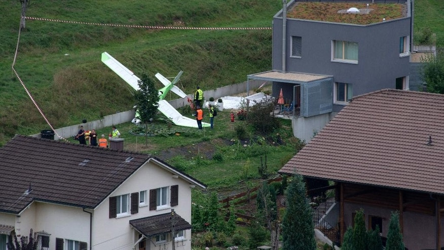 Firefighter stand beside a crashed plane crash, Sunday, 23 August 2015, in Dittingen, Switzerland. Two small planes crashed into each other just at an airshow in Dittingen, Switzerland, killing at least one person. (Georgios Kefalas/Keystone via AP)