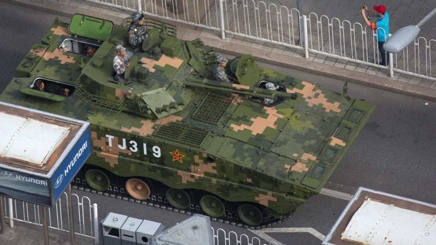 A Chinese armored fighting vehicle leaves after rehearsals ahead of the Sept. 3 military parade to commemorate the end of World War II in Beijing, Sunday, Aug. 23, 2015. China is ramping up publicity for its upcoming massive military parade but officials still aren't saying what other countries are taking part. (AP Photo/Ng Han Guan)