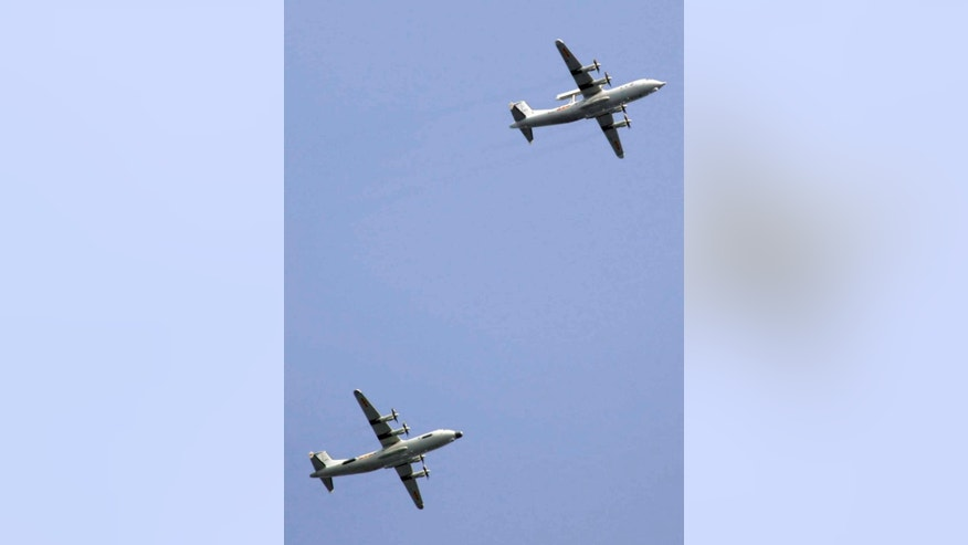 Chinese military planes fly in formation during a rehearsal ahead of the Sept. 3 military parade to commemorate the end of World War II in Beijing, Sunday, Aug. 23, 2015. China is ramping up publicity for its upcoming massive military parade but officials still aren't saying what other countries are taking part.  (AP Photo/Mark Schiefelbein)