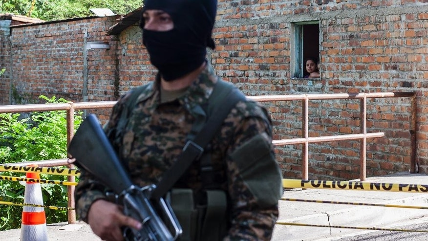 A resident peers from her home where a masked soldier stands guard near a prison in Quezaltepeque, El Salvador, Sunday, Aug. 23, 2015. At least 14 gang members held at the prison facility located just northwest of San Salvador were killed in violence that authorities blame on a conflict within a faction of the Barrio 18 gang. (AP Photo/Salvador Melendez)