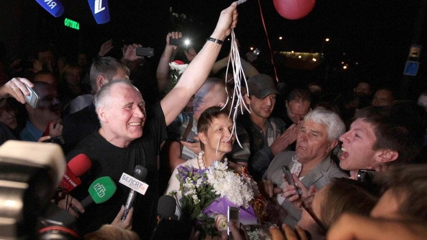 A former opposition presidential candidate Nikolai Statkevich, left, meets with supporters at a bus station as he was released from a prison, Minsk, Belarus, late Saturday, Aug. 22, 2015. The authoritarian president of Belarus on Saturday pardoned all six political prisoners in the former Soviet republic, including Statkevich, a former opposition presidential candidate. (AP Photo)