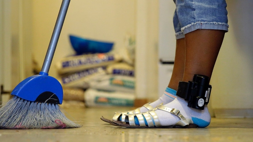 An immigrant from Honduras who entered the United States illegally wears an ankle monitor as she sweeps the floor during her stay at a respite house, Tuesday, Aug. 18, 2015, in San Antonio. Immigration authorities have banned two lawyers from the nationâs largest immigrant family detention center, saying they violated standards. But a coalition of immigration attorneys says the moves are unprecedented and is fighting to rescind the bans as part of its ongoing effort to improve access to clients, a key factor in whether asylum cases are allowed to proceed. (AP Photo/Eric Gay)