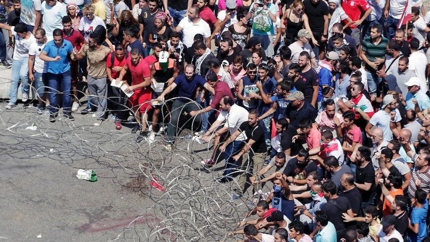 Lebanese activists try to remove a barbed wire barrier to cross to the government house, during a protest against the ongoing trash crisis, in downtown Beirut, Lebanon, Sunday, Aug. 23, 2015. Lebanon's prime minister Tammam Salam hinted Sunday he might resign after violent protests against government corruption and political dysfunction triggered by a monthlong trash crisis in Beirut. Salam also pledged that security forces that used violence against demonstrators would be held accountable. (AP Photo/Bilal Hussein)