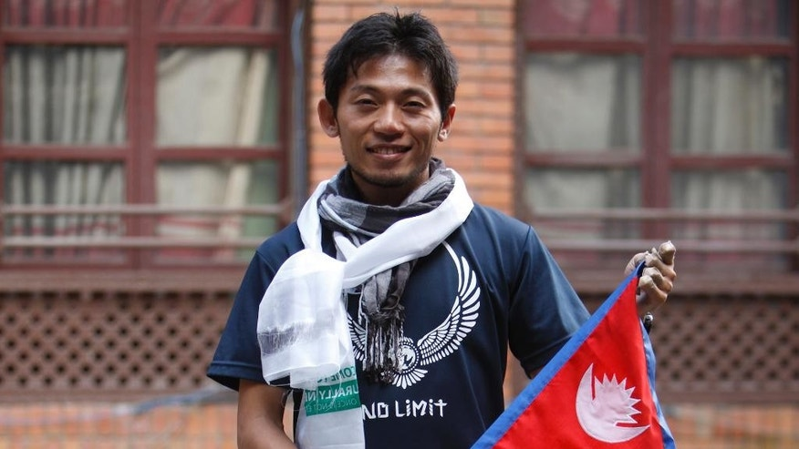 Japanese climber Nobukazu Kuriki poses with a Nepalese flag during a press conference in Kathmandu, Nepal, Sunday, Aug. 23, 2015.Nepal has opened Mount Everest to climbers for the first time since an earthquake-triggered avalanche in April killed 19 mountaineers and ended the popular spring climbing season. Kuriki will be the first to attempt to scale the world's highest peak since the quake. Nepal's tourism minister, Kripasur Sherpa, gave Kuriki his climbing permit at a ceremony in Kathmandu on Sunday. (AP Photo/Bikram Rai)