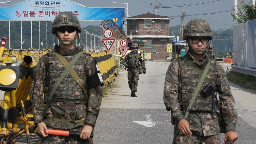 Aug. 23, 2015: A South Korean amy soldier walks as his colleague soldiers stand guard on Unification Bridge, which leads to the demilitarized zone, near the border village of Panmunjom in Paju, South Korea.