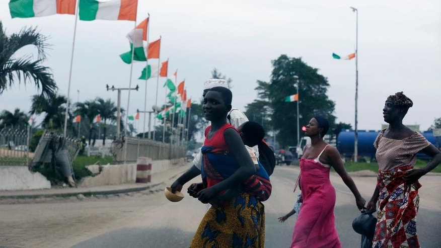 In this photo taken Wednesday, Aug. 19, 2015, pedestrians cross a main road with Ivorian flags in the background, in Abidjan, Ivory Coast. Ivory Coast taxi driver Mamadou Bamba had finished his shift and was walking home around midnight when a dozen children accosted him on the street and demanded his money. When he hesitated, the thieves pulled out small knives and stabbed him eight times before making off with fares totaling more than $100.  (AP Photo/Sunday Alamba)