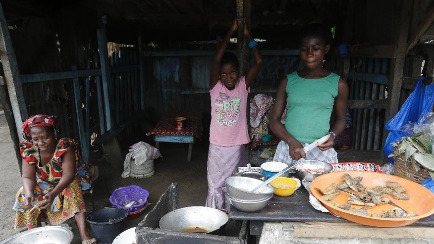In this photo taken Wednesday, Aug. 19, 2015, women sell fish on a street in Abobo neighborhood, were child thieves attacked a resident recently, in Abidjan,  Ivory Coast. Ivory Coast taxi driver Mamadou Bamba had finished his shift and was walking home around midnight when a dozen children accosted him on the street and demanded his money. When he hesitated, the thieves pulled out small knives and stabbed him eight times before making off with fares totaling more than $100.  (AP Photo/Sunday Alamba)