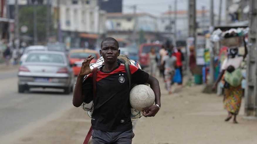 In this photo taken Wednesday, Aug. 19, 2015, a man sells soccer balls on a street in Abobo neighborhood, were child thieves attacked a resident recently, in Abidjan,  Ivory Coast. Ivory Coast taxi driver Mamadou Bamba had finished his shift and was walking home around midnight when a dozen children accosted him on the street and demanded his money. When he hesitated, the thieves pulled out small knives and stabbed him eight times before making off with fares totaling more than $100.  (AP Photo/Sunday Alamba)