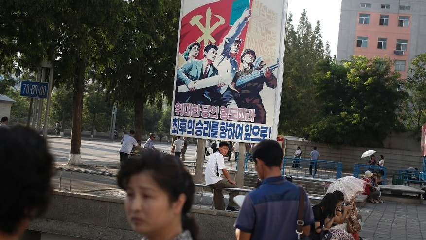 A man sits under a propaganda banner in Pyongyang, North Korea, Sunday, Aug. 23, 2015. North and South Korea on Sunday resumed a second round of talks that temporarily pushed aside vows of imminent war on the peninsula. (AP Photo/Dita Alangkara)