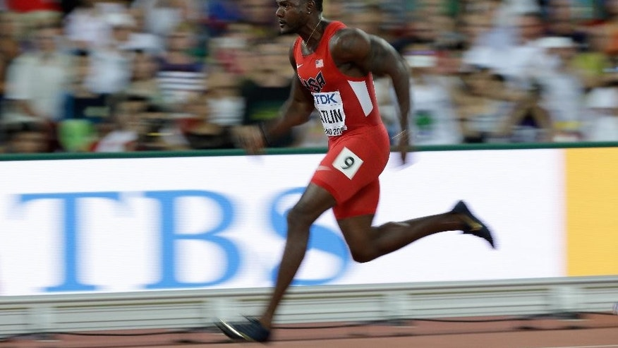 United States' Justin Gatlin competes in round one of the men's 100m at the World Athletics Championships at the Bird's Nest stadium in Beijing, Saturday, Aug. 22, 2015. (AP Photo/Lee Jin-man)