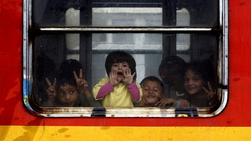 Children migrants look from a window onboard a train departing towards Serbia, at the railway station in the southern Macedonia's town of Gevgelija, on Saturday, Aug. 22, 2015. Thousands of rain-soaked migrants on Saturday rushed past Macedonian riot police who were attempting to block them from entering Macedonia from Greece.  (AP Photo/Boris Grdanoski)