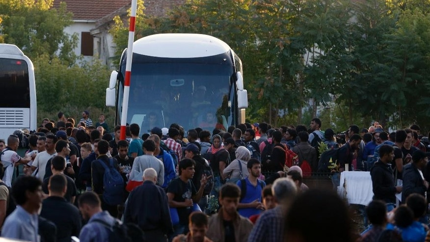Migrants at the bus station in the southern Macedonian town of Gevgelija, Saturday, Aug. 22, 2015. Thousands of rain-soaked migrants on Saturday rushed past Macedonian riot police who were attempting to block them from entering Macedonia from Greece. (AP Photo/Darko Vojinovic)