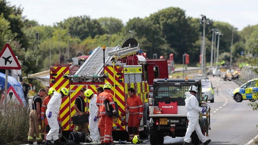 Emergency services attend the scene where seven people died when an historic Hawker Hunter fighter jet plane plummeted onto the major south coast road on Saturday, after failing to pull out of a loop manoeuvre, at Shoreham, England, on Sunday Aug. 23, 2015.  Investigators and emergency services continue to search the scene of the Shoreham Airshow plane crash, police said. (Daniel Leal-Olivas/PA via AP) UNITED KINGDOM OUT - NO SALES - NO ARCHIVES