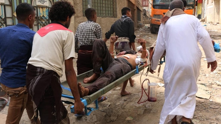 People carry a man who was injured during fighting between tribal fighters and Shiite rebels known as Houthis in Taiz, Yemen, Sunday, Aug. 23, 2015. Yemen's conflict pits the Iran-allied Houthis and troops loyal to the former president, Ali Abdullah Saleh, against an array of forces including southern separatists, local and tribal militias, Sunni Islamic militants as well as troops loyal to President Abed Rabbo Mansour Hadi. (AP Photo/Abdulnasser Alseddik)