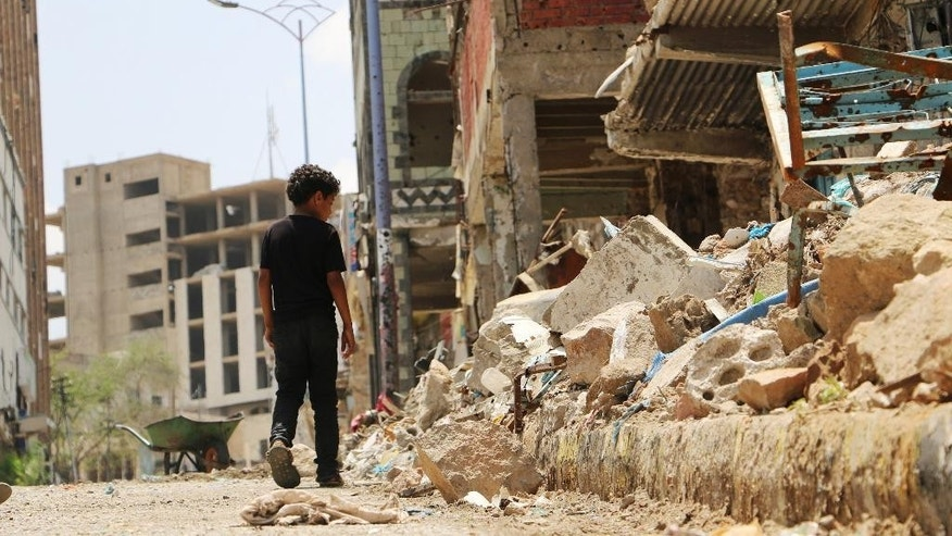 A boy walks near the rubbles of houses destroyed during fighting between tribal fighters and Shiite rebels known as Houthis in Taiz, Yemen, Sunday, Aug. 23, 2015. Yemen's conflict pits the Iran-allied Houthis and troops loyal to the former president, Ali Abdullah Saleh, against an array of forces including southern separatists, local and tribal militias, Sunni Islamic militants as well as troops loyal to President Abed Rabbo Mansour Hadi. (AP Photo/Abdulnasser Alseddik)