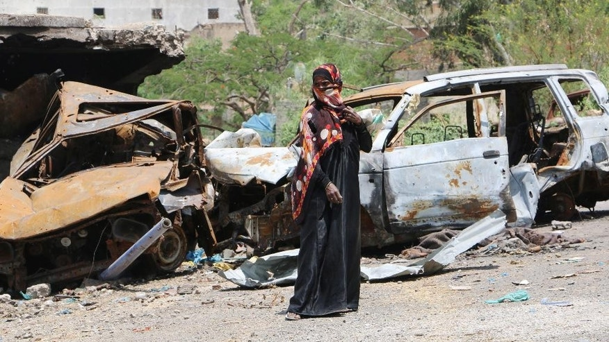 A woman stands next to cars destroyed during fighting between tribal fighters and Shiite rebels known as Houthis at a street in Taiz, Yemen, Sunday, Aug. 23, 2015. Yemen's conflict pits the Iran-allied Houthis and troops loyal to the former president, Ali Abdullah Saleh, against an array of forces including southern separatists, local and tribal militias, Sunni Islamic militants as well as troops loyal to President Abed Rabbo Mansour Hadi. (AP Photo/Abdulnasser Alseddik)