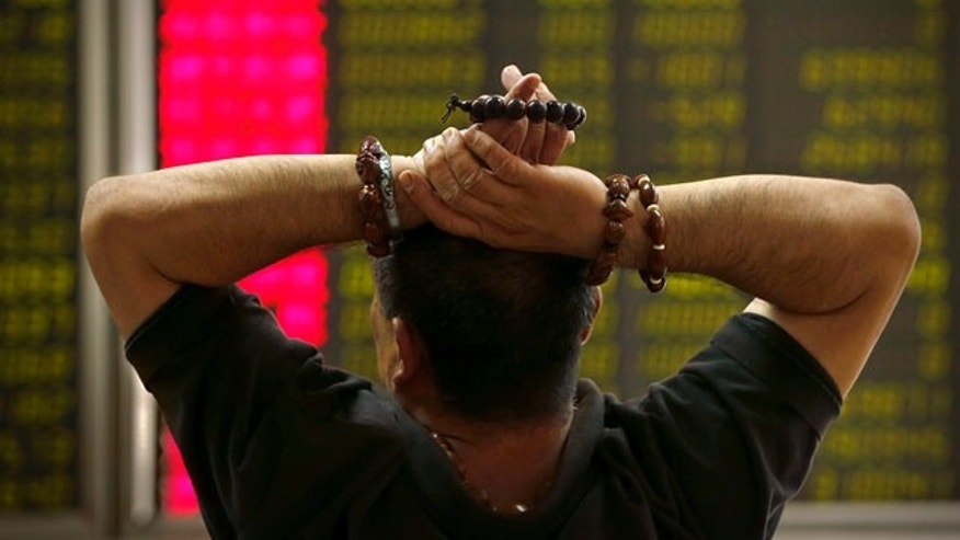 Aug. 24, 2015: A Chinese investor monitors stock prices at a brokerage house in Beijing. Stocks tumbled across Asia on Monday as investors shaken by the sell-off last week on Wall Street unloaded shares in practically every sector. (AP Photo/Mark Schiefelbein)