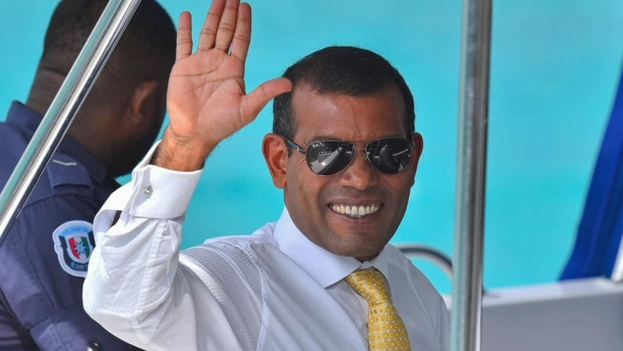 FILE- In this March 15, 2015 file photo, Maldives former President Mohamed Nasheed waves sitting in a boat as he is taken back to Dhoonidhoo prison after a court dismissed his appeal against his arrest in Male, Maldives. A party spokesman says Maldives police have taken Nasheed back to jail Sunday night even though his detention was formally commuted to house arrest last month. (AP Photo/ Mohamed Sharuhaan, file)