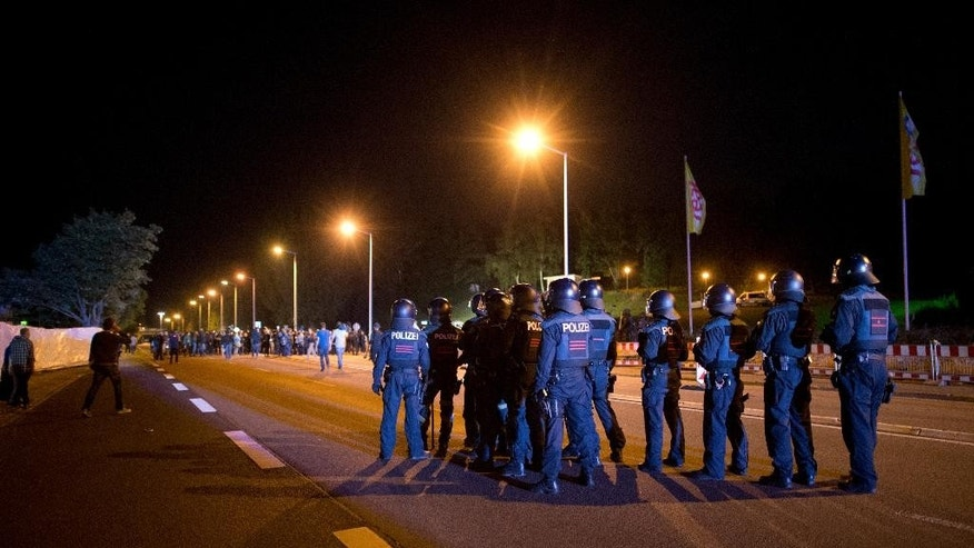 In this Aug. 23, 2015 photo police secure the street in front of a former DIY market that has been converted into an asylum seeker home as leftist demonstrators gather nearby in Heidenau, south of Dresden, eastern Germany. (Arno Burgi/dpa via AP)