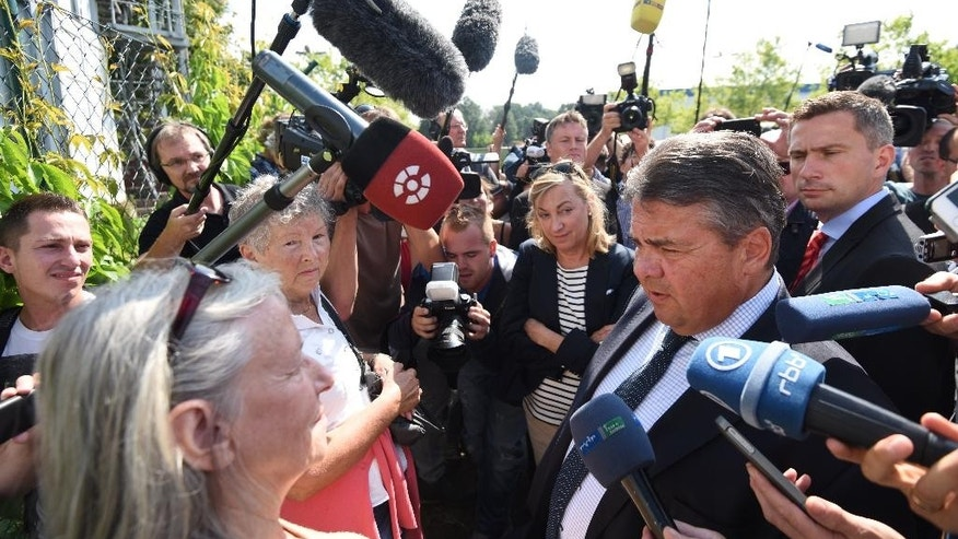 Germany's vice-chancellor, Sigmar Gabriel, second right, talks to journalists as he visits a refugee shelter that was attacked by far-right protesters over the weekend in Heidenau, eastern Germany, Monday Aug. 24, 2015.  (Rainer Jensen/dpa via AP)