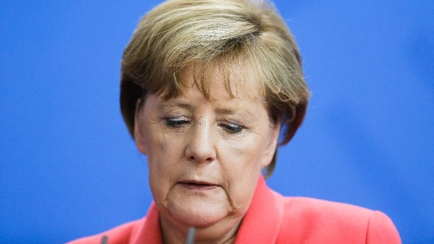 German Chancellor Angela Merkel addresses the media during a statement with French President Francois Hollande about the European migrant crisis prior to a meeting at the chancellery  in Berlin, Monday, Aug. 24, 2015. (AP Photo/Markus Schreiber).
