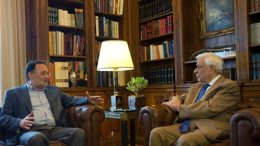 Former Energy Minister and head a party called Popular Unity, Panagiotis Lafazanis, left , chats  with Greek President Prokopis Pavlopoulos, in Athens, Monday Aug. 24, 2015. Lafazanis, who heads the newly-formed Popular Unity, received the maximum three-day mandate from the country's president after the head of the main opposition conservative New Democracy failed to form a government.  (AP Photo/Petros Giannakouris)
