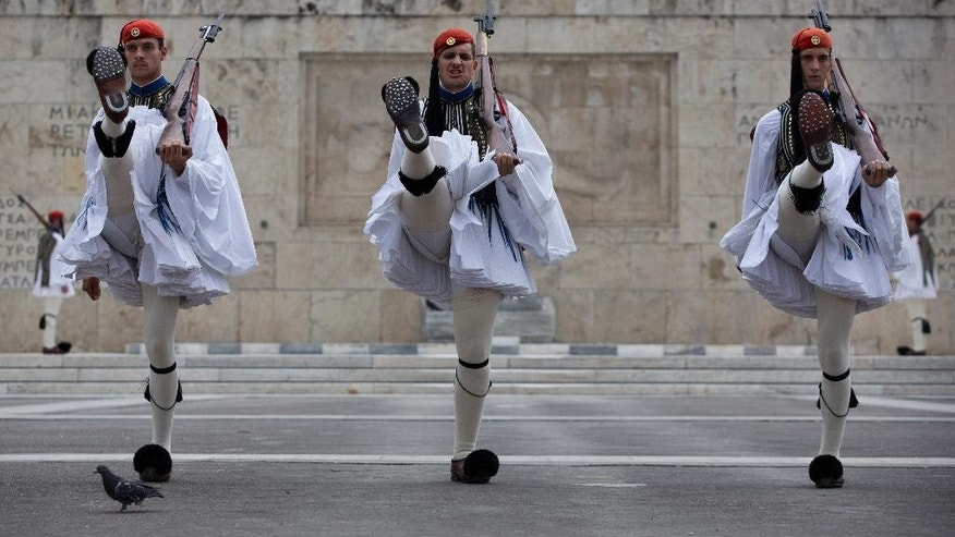 Greek presidential guards perform during the changing of the guards ceremony at the tomb of the unknown soldier in central Athens, on Sunday, Aug. 23, 2015. Greece's Prime Minister Alexis Tsipras resigned late Thursday and called an early election next month to deal with a rebellion in his radical left Syriza party over the terms of Greece's new bailout deal.  (AP Photo/Petros Giannakouris)