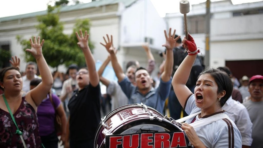 People gather in front of  the Presidential House in Guatemala City, Sunday, Aug. 23, 2015, demanding the resignation of Guatemala's President Otto Perez Molina as  he and his staff  meet inside.  Perez Molina's former Vice President Roxana Baldetti was detained Friday in connection with a customs corruption scandal that led to her resignation. Prosecutors also announced they are seeking to investigate the president in the matter. (AP Photo/Moises Castillo)