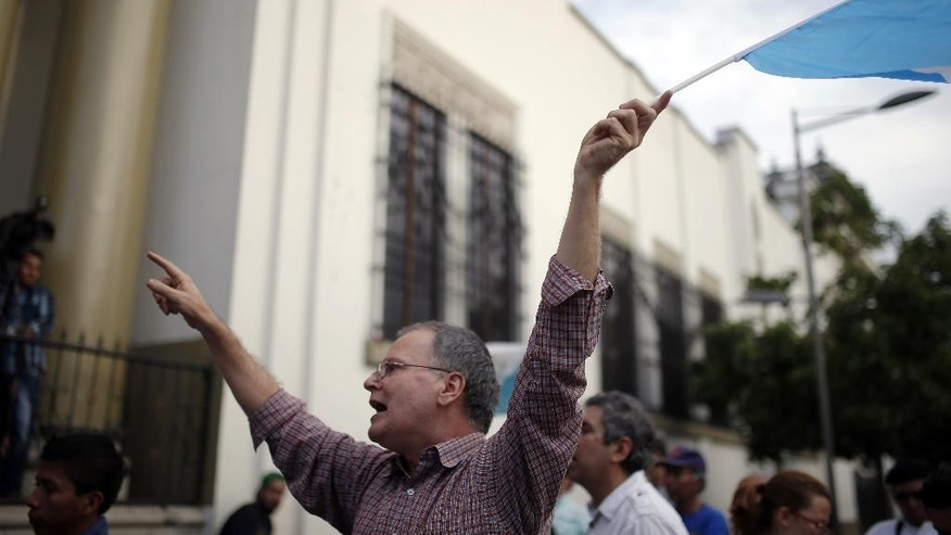 A man waves a Guatemalan flag during a protest in front of the Presidential House demanding the resignation of Guatemala's President Otto Perez Molina in Guatemala City, Sunday, Aug. 23, 2015. Perez Molina's former Vice President Roxana Baldetti was detained Friday  in connection with a customs corruption scandal that led to her resignation.  (AP Photo/Moises Castillo)