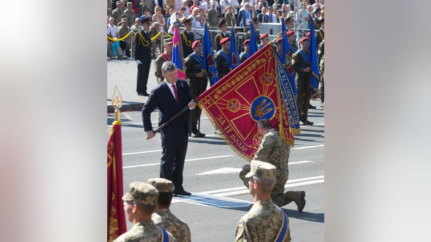 Ukraine's President Petro Poroshenko hands over a flag of a military unit as a soldier kisses the flag before a military parade on the occasion of Ukraine's Independence Day in the capital Kiev, Ukraine,  Monday, Aug. 24, 2015. Speaking at the parade, President Petro Poroshenko said Ukraine would continue to increase its troop numbers in order to fend off the attacks of separatist rebels.(AP Photo/Efrem Lukatsky)