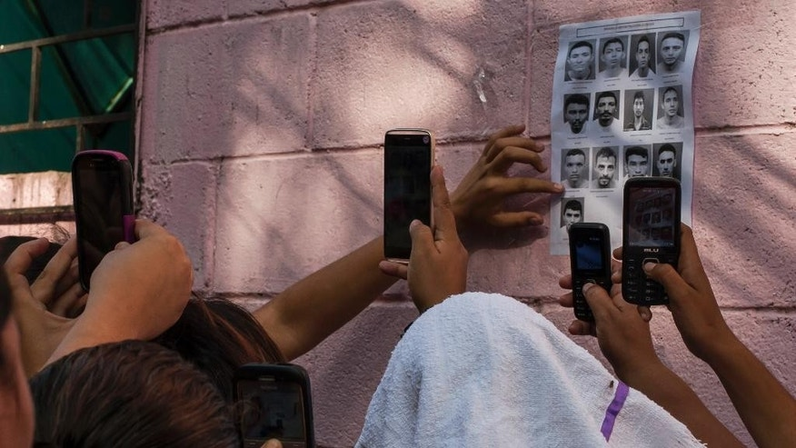 The relatives of inmates take photos of portraits of killed inmates as they wait outside the prison for more information in Quezaltepeque, El Salvador, Sunday, Aug. 23, 2015. Over a dozen gang members held at the prison, located just northwest of the capital, were killed in violence that authorities blame on a conflict within a faction of the Barrio 18 gang. (AP Photo/Salvador Melendez)