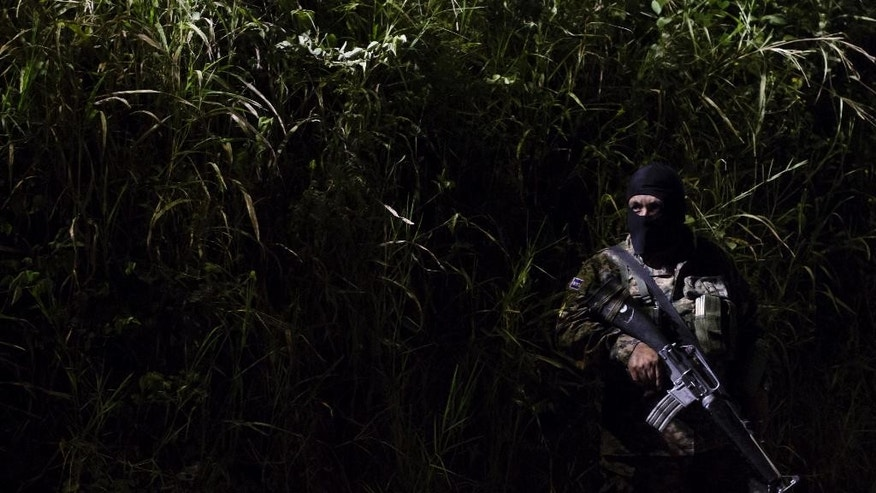 A masked soldier stands guard outside the prison in Quezaltepeque, El Salvador, early Sunday, Aug. 23, 2015. Over a dozen gang members held at the prison facility, located just northwest of the capital, were killed in violence that authorities blame on a conflict within a faction of the Barrio 18 gang. (AP Photo/Salvador Melendez)