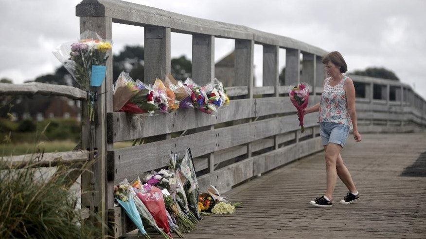 "A woman lays flowers on the Shoreham Tollbridge that crosses the River Adur near the location where a Hawker Hunter fighter jet crashed on a busy road near Shoreham-by-sea, West Sussex, England, Sunday, Aug. 23, 2015. British police on Sunday said the death toll from an airshow crash is ""highly likely"" to increase after a fighter jet slammed into a busy main road on Saturday. The initial death toll was seven. (Daniel Leal-Olivas/PA Wire via AP) UNITED KINGDOM OUT, NO SALES, NO ARCHIVE"