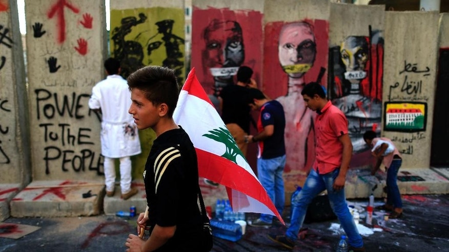 "Lebanese activists protest in front a concrete wall installed by authorities, and quickly covered with graffiti, near the main Lebanese government building a day after violent anti-government protests, in downtown Beirut, Lebanon, Monday, Aug. 24, 2015. Organizers of the ""You stink"" protests that have captivated the Lebanese capital postponed anti-government demonstrations set for Monday evening after a night of violent clashes with police during which dozens of protesters and police officers were wounded. (AP Photo/Hassan Ammar)"