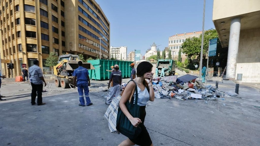 "A woman covers her nose as she passes by waste management workers as they collect a pile of garbage near the government building a day after a violent protests against the ongoing trash crisis, in downtown Beirut, Lebanon, Monday, Aug. 24, 2015. Organizers of the ""You stink"" protests that have captivated the Lebanese capital postponed demonstrations set for Monday evening after a night of violent clashes with police during which dozens of protesters and police officers were wounded. (AP Photo/Hassan Ammar)"