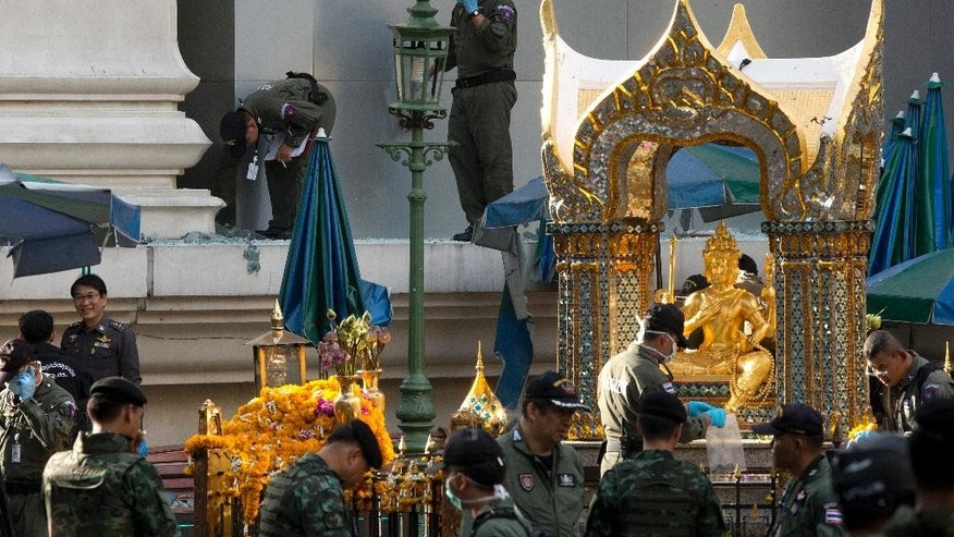 "FILE - In this Aug. 18, 2015 file photo, police investigate the scene around the Erawan Shrine the morning after an explosion in Bangkok,Thailand.   National police chief Somyot Poompanmoung said Monday, Aug. 24,2015,  that police were trying to ""put pieces of the puzzle together"" but had to use their imagination to fill holes where street-side security cameras were broken and unable to record the suspect's movements. (AP Photo/Mark Baker, File)"