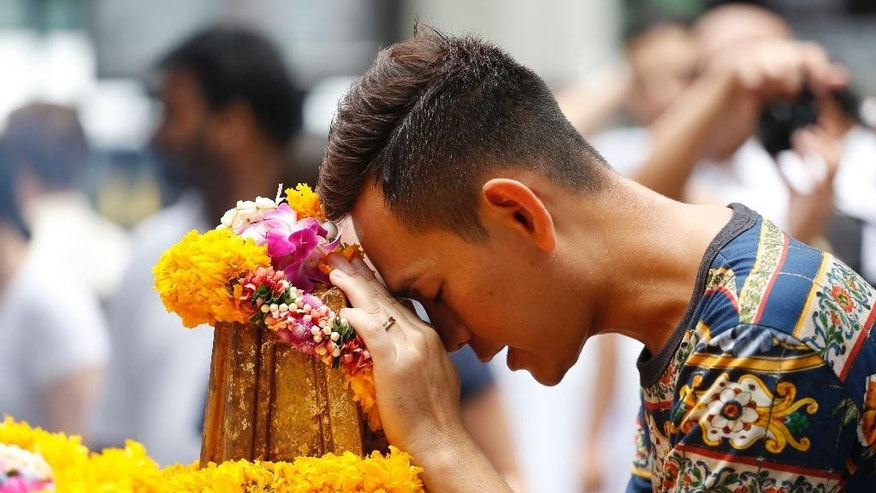 A man prays at the Erawan Shrine at Rajprasong intersection, the scene of last week's bombing, in Bangkok, Thailand, Monday, Aug. 24, 2015. One week after last Monday's bombing at the capital's revered Erawan Shrine, which left 20 people dead and scores injured, police appeared no closer to tracking down suspects or determining a motive for the attack. (AP Photo/Sakchai Lalit)