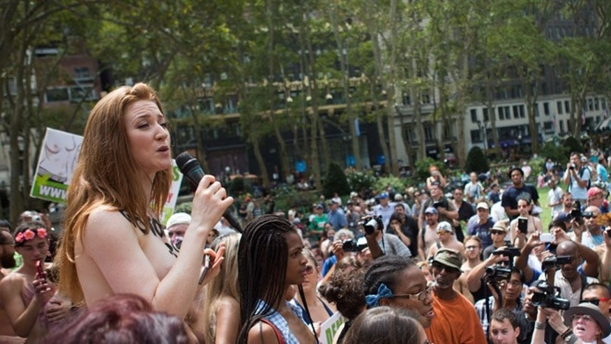 EDS NOTE: NUDITY - Rachel Jessee speaks to a crowd, consisting mainly of photographers, during a media event following the GoTopless Day Parade in Bryant Park, Sunday, Aug. 23, 2015, in New York. The parade took to the streets to counter critics who are complaining about topless tip-seekers in Times Square. Appearing bare-breasted is legal in New York. But Mayor Bill de Blasio and police Commissioner Bill Bratton say the body-painted women in the square who take photos with tourists are a nuisance. (AP Photo/Kevin Hagen)