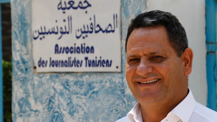 Neji Bghouri, the head of Tunisia's journalists' union poses for a portrait in front of his office after discussing the new threats to free expression in Tunis, Tunisia, Sunday Aug. 8, 2015. Seven men spent a week in prison on terrorism charges, suffering what they claim was torture under custody, before a judge released them for lack of evidence. But as they stepped out of the courthouse in early August, plainclothes policemen swooped in and spirited them away. (AP Photo/Paul Schemm)