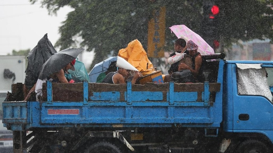 Filipinos riding on a truck take cover during rain from an enhanced southwest monsoon in Manila, Philippines on Monday, Aug. 24, 2015 as Typhoon Goni exits the country. In the Philippines, Goni dumped heavy rain for three days on the mountainous north, then battered already-sodden upland villages with fierce winds, triggering landslides, officials said. (AP Photo/Aaron Favila)