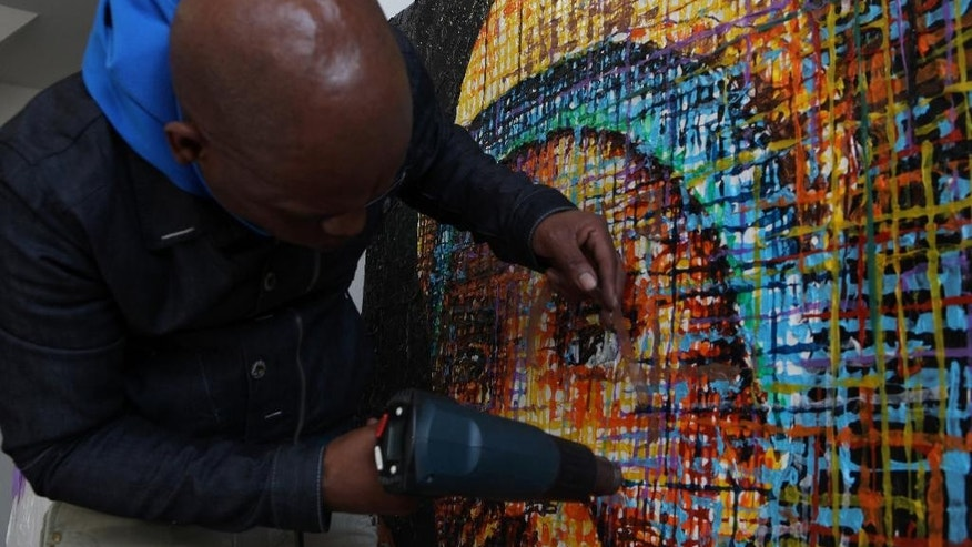 FILE - In this file photo taken Tuesday, June 9, 2015 South African artist Mbongeni Buthelezi works on a portrait in his Johannesburg Studio.  Buthelezi is turning discarded bits of plastic into sought-after works of art. The plastic bubbles pop under Buthelezi's fingertips, calloused from manipulating the hot, molten material he uses to create large abstract pieces and portraits. (AP Photo/Denis Farrell)